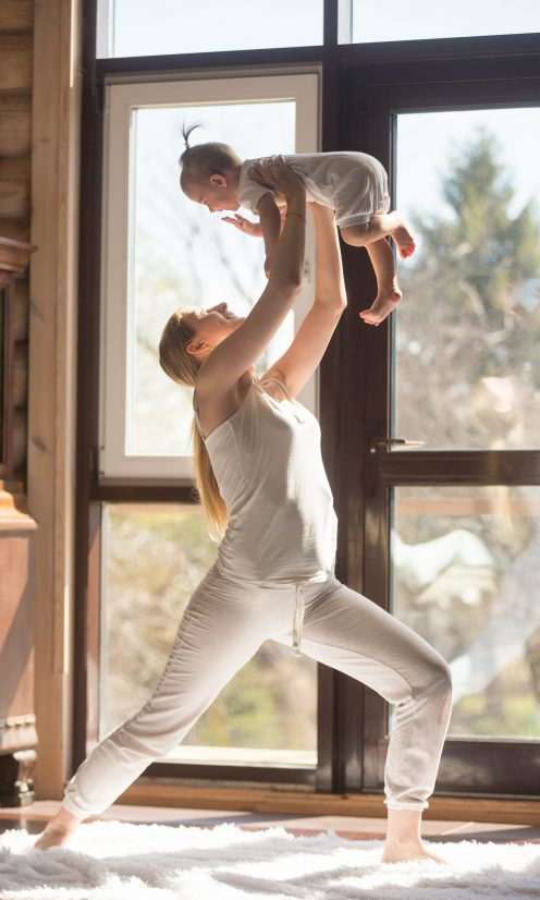 Young attractive sporty mother doing exercises with her baby at home, wearing white sportswear, standing and holding her baby daughter high, playful interaction and communication, fun and fitness time