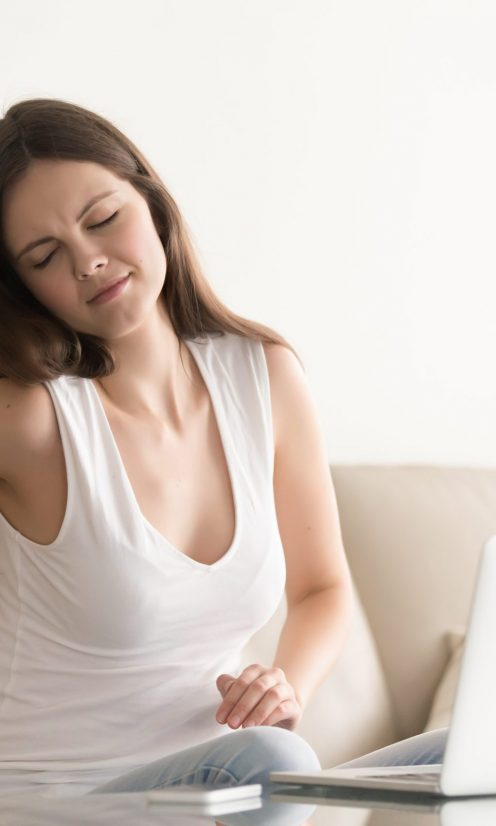 Woman sitting on sofa stretching and rubbing stiff back muscles after too much computer work on. Stressed lady suffering from backache after sedentary work, feels discomfort because of posture problem